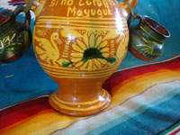 Mexican vintage pottery and ceramics, and Mexican vintage folk art, a lovely pottery chicken, holding two hanging cups for Tequila or Mescal, the state of Michoacan, c. 1950's.  A closeup view of the front bottom of the Mexican pottery chicken with cups, showing the very fine artwork.