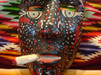 Mexican vintage woodcarvings and masks, a hand-carved and decorated mask of the Negrito, for the dance of the Negritos, Michoacan, c. 1950's. Closeup photo of the mouth and cigarette.