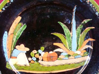 Mexican vintage pottery, a blackware plate from Tlaquepaque, Jalisco, c. 1930's. It features a very beautiful rural scene and a wonderful floral border. Closeup photo of central design of plate.