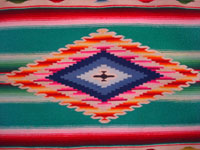 Mexican vintage textiles and sarapes, a wonderful Saltillo sarape with a fine center diamond, c. 1920. The center diamond and the decorative side-bars contain very fine silk. Closeup photo of the center medallion of the sarape.