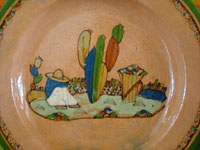 Mexican vintage pottery and ceramics, a lovely terra-cota plate from Tlaquepaque, Jalisco, c. 1940. The peach-colored background glazing is beautiful. The scene on the plate is exceptional; it features a snoozing campesino in a wonderful rural setting. Closeup of the central design, showing the snoozing campesino amidst rocks and plants.