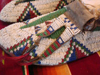 Native American Indian antique beadwork, a pair of Sioux (Lakota) beaded mocassins, c. 1890. The beadwork is exceptionally fine. The mocassins have a bi-furcated tongue. Closeup photo.