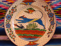Mexican vintage pottery and ceramics, a very fine pottery plate featuring a leaping wolf, a blue bunny, butterflies and lovely foliage, with a starry-night background, from Tlaquepaque, Jalisco, c. 1920's. Closeup photo of the front of the plate.
