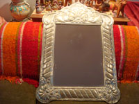 Mexican vintage tin-work art and silver art, a mirror, framed with beautifully stamped silver, Mexico, c. 1950's. Main photo of the mirror with the stamped silver frame.