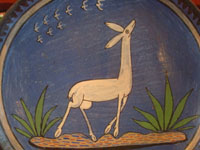 Mexican vintage pottery and ceramics, a lovely burnished plate with a beautiful blue background and wonderful artwork, Tonala or Tlaquepaque, Jalisco, c. 1930's. The artwork features a very graceful and elegant deer.  Closeup photo of the lovely deer on the plate.