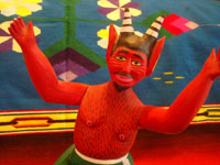 Mexican vintage folk art, and Mexican vintage woodcarvings and masks, a folk art woodcarving depicting an animated red devil with a lucha libre -like stance, signed Isaias Jimenez, son of the famous Manuel Jimenez of Oaxaca, c. 1960. Closeup photo of the devil's face.