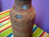 Native American Indian antique baskets, a Tlingit hand-blown glass bottle with wonderful weaving around it, c. 1900. Photo of another side of the bottle showing some of the damage.