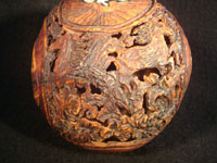 Mexican vintage folk art, a finely carved coconut with scenes from the Mexican Revolution of 1910, c. 1925-35. The carved coconut has the Mexican national emblem of the eagle and snake inlaid in abalone. Photo of back of carved coconut.