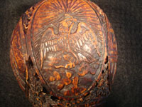 Mexican vintage folk art, a finely carved coconut with scenes from the Mexican Revolution of 1910, c. 1925-35. The carved coconut has the Mexican national emblem of the eagle and snake inlaid in abalone. Closup photo of Mexican eagle.