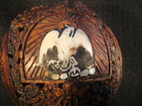 Mexican vintage folk art, a finely carved coconut with scenes from the Mexican Revolution of 1910, c. 1925-35. The carved coconut has the Mexican national emblem of the eagle and snake inlaid in abalone. Closeup photo of Mexican flag inlaid in abalone.