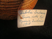 Native American Indian antique basket, Mission basket with original sales tag, 1918. Very finely woven Mission basket with the original sales tag from c. 1918. Various shades of juncus on a deer grass bundle; very tightly coiled. The original sales tag identifies this basket as from the Saboba Reservation, Riverside, California, 1918. The other side of the tag identifies the basket as coming from a Marvin Whitaker of Portland, Oregon, the dealer or original collector. Condition is excellent. Photo of the original sales tag from this Mission Indian basket.