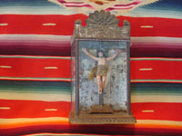 Mexican vintage devotional art, a carved wooden figure of the crucified Christ in a tinwork and glass nicho, c. 1920. The wood carving is covered with gezzo and very beautifully painted. Main photo of the retablo.