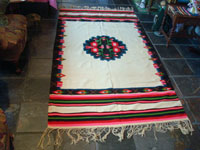 Mexican vintage textiles and sarapes, a lovely weaving from Oaxaca, c. 1940's. The textile is beautifully woven of fine wool. It has a white background with lovely flowers in the border and a beautiful center medallion. Another photo of the entire textile.