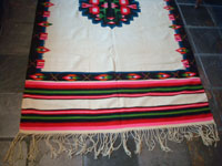 Mexican vintage textiles and sarapes, a lovely weaving from Oaxaca, c. 1940's. The textile is beautifully woven of fine wool. It has a white background with lovely flowers in the border and a beautiful center medallion. Photo of one end showing the fringe.