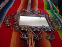 Mexican vintage tinwork-art (tin-art), a beautiful tinwork-art mirror, c. 1940's. The mirror has very fine tinwork-art and is very graceful in shape. A side view of the Mexican tinwork-art (tin-art) mirror.