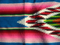Mexican vintage textiles and Saltillo serapes, and Mexican vintage blouses and huipiles, a beautiful Saltillo serape (sarape) with a lovely turquoise background and a wonderful woolen and silk center medallion, c. 1930's. Closeup photo of one edge of the center medallion of the Saltillo serape (sarape).