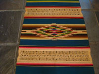 Mexican vintage textiles and Saltillo serapes (sarapes), a magnificent Saltillo serape runner with three lovely medallions and the teneriffe lace or macrome panels, c. 1930's.  Closeup photo of the middle of the serape.