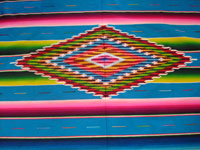 Mexican vintage sarape and textile, a Saltillo sarape, c. 1930's. Beautiful turquoise field. Very finely woven of wool and with a dynamite center diamond and end-bars of silk. Photo of center medallion.
