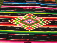 Mexican vintage textiles, and Mexican vintage Saltillo serapes (sarapes), a wonderful Saltillo serape with a black background and a very colorful center medallion of fine silk, c. 1930's. Closeup photo of the center medallion of the serape.