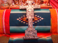 Mexican vintage devotional art, and Mexican vintage folk art, a black, wooden cross covered with hundreds of silver milagros covering three sides of the cross and on the bottoms of the side arms of the cross, c. 1970's. Main photo of the Mexican cross with hundreds of silver milagros.