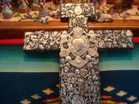 Mexican vintage devotional art, and Mexican vintage folk art, a black, wooden cross covered with hundreds of silver milagros covering three sides of the cross and on the bottoms of the side arms of the cross, c. 1970's. Closeup photo of the center of the milagro cross.