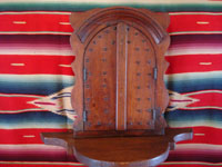 Mexican vintage devotional art, and Mexican vintage woodcarving and woodwork, a very beautiful wooden nicho whose two doors open to reveal a very fine retablo depicting the Holy Trinity, painted on tin, c. 1920-30's. A closeup photo of the front of the nich, with doors closed.