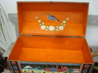Mexican vintage folk art, and Mexican vintage woodcarvings and masks, a truly beautiful, large arcon, or trunk, of black laquered wood, with incredible artwork, Olinala, c. 1930's. A photo of the painted orange inside of the trunk with the lid open.