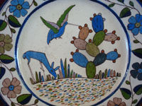 Mexican vintage pottery and ceramics, a beautiful Tlaquepaque pottery plate with a wonderful border surrounding a scene of a deer and a hummingbird, Tonala or San Pedro Tlaquepaque, Jalisco, c. 1940's. Closeup photo of the hummingbird and deer on the front of the plate.