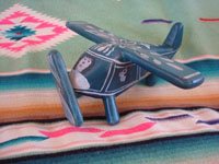 Mexican vintage folk art, and Mexican vintage woodcarvings and masks, a whimsical and lovely laquered woodcarving of an airplane with 4 happy passengers, Olinala, c. 1950's. Main photo of the front of the Olinala laquered airplane.