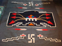 New Mexican vintage textile, a finely woven rug from the weaving center of Chimayo, New Mexico, c. 1930. This is from a very famous weaver, active from 1910-40, whose signature was the hummingbird in the center of this textile. Photo of hummingbird in center of textile.