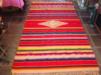 Mexican vintage textiles and sarapes, a beautiful Saltillo sarape with a red background, c. 1940's. The center medallion is spectacular, and the colors on both front and back are bright and vibrant. Main photo of the Saltillo sarape.