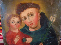 Mexican vintage devotional art and tinwork-art, a beautiful retablo painted on tin, depicting St. Anthony of Padua and the Child Jesus, c. 1910-20. Closeup photo of the faces of St. Anthony and the Child Jesus on the tin retablo.