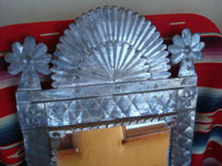 Mexican vintage tinwork art (tin art), a beautiful tinwork art mirror with a lovely form and very good stamping, c. 1940's. The shape of the mirror reflects the form of the facade of a church. Closeup photo of the top of the tinwork art mirror.