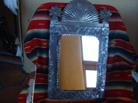 Mexican vintage tinwork art (tin art), a beautiful tinwork art mirror with a lovely form and very good stamping, c. 1940's. The shape of the mirror reflects the form of the facade of a church. Another photo of the tin art mirror.