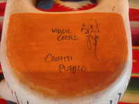 Native American Indian folk art, and Native American Indian pottery and ceramics, a wonderful, very whimsical pottery figure depicting an Anglo or European visitor or clown, signed by the famous artist, Virgil Ortiz, Cochiti Pueblo, c. 1980. Photo showing the bottom of the figure, showing the artist's signature, Virgil Ortiz, Cochiti Pueblo.