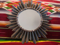 Mexican tinwork art, a wonderful tinwork-art mirror with the shape of a lovely sunburst, Mexico, c. 1950's. Main photo of the sunbust tinwork-art mirror.