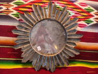 Mexican tinwork art, a wonderful tinwork-art mirror with the shape of a lovely sunburst, Mexico, c. 1950's. A photo showing the back side of the mirror.