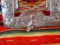 Mexican vintage tinwork-art, a beautifully stamped tin-work frame, c. 1950. The stamping work on this tin frame is magnificent, and features lovely cherubs and angels. Another closeup photo.
