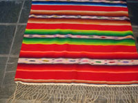 Mexican vintage textiles and Saltillo sarapes (serapes), a beautiful Saltillo sarape (serape, English spelling) with bright colors and a wonderful center diamond, c. 1930's. Photo showing one edge of the serape with fringe.