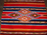 Mexican vintage textiles and Saltillo sarapes (serapes), a beautiful Saltillo sarape (serape, English spelling) with bright colors and a wonderful center diamond, c. 1930's. Closeup photo of the center medallion of the Saltillo serape (sarape).