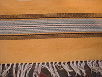 New Mexican vintage textiles, a finely woven woolen textile from Chimayo, New Mexico, with a rare mustard-colored background, c. 1940's. Closeup photo of one edge of the Chimayo textile showing the fine fringe.