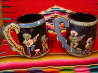 Mexican vintage pottery and ceramics, a wonderful pair of pottery mugs, with musicians, couples dancing, men drinking their tequila, all in relief and with beautiful animation and colors against a black background, Tonala or Tlaquepaque, Jalisco, c. 1930's.  Photo of the second side of the mugs.