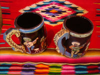 Mexican vintage pottery and ceramics, a wonderful pair of pottery mugs, with musicians, couples dancing, men drinking their tequila, all in relief and with beautiful animation and colors against a black background, Tonala or Tlaquepaque, Jalisco, c. 1930's.  Another angle of the mugs.