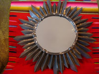Mexican vintage tinwork art, a lovely tinwork art mirror resembling a beautiful sunburst, c. 1940's. Main photo of the mirror.