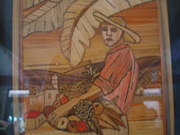 Close-up photo of straw-art picture of man with basket of fruit.