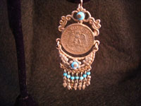 Closeup photo of Mexican coin earrings.