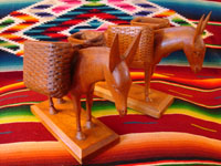 Mexican vintage wood-carvings, a pair of burros with baskets across their backs, c. 1940.