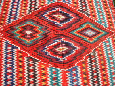 Mexican vintage sarapes (serapes) and textiles, a lovely post-classic Saltillo sarape woven in two panels, with vivid and wonderful colors, c. 1880-1900. The vivid colors are of indigo blue, cochineal red, with other natural dyes. Closeup photo of the center medallion.