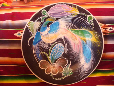 Mexican vintage pottery and ceramics, a lovely pottery charger with a black background and decorated with a beautiful and graceful exotic bird or egret, Tonala, Jalisco, c. 1950's.